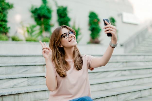 Ragazza graziosa che fa selfie all'aperto
