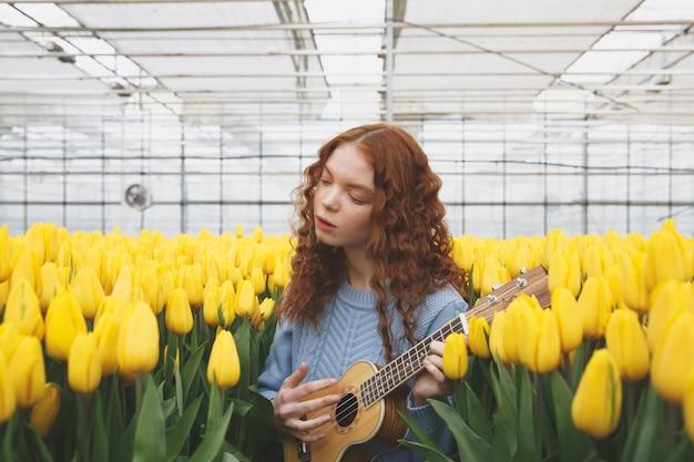 Ragazza graziosa che gioca chitarra mentre stando fra i tulipani gialli in serra