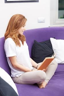 Ragazza graziosa che legge un libro sul sofà viola