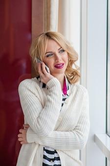 Ragazza graziosa che parla sul telefono vicino ad una finestra, bionda