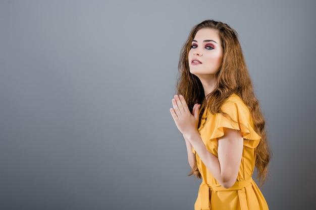 Ragazza graziosa che porta vestito giallo che spera e che prega isolato sopra grey