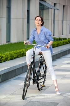 Ragazza graziosa che si siede su una bicicletta alla via