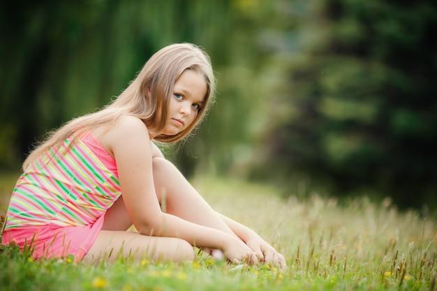 Ragazza graziosa che si siede sull'erba verde all'aperto
