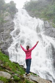 Ragazza graziosa che sta con le mani sollevate alla grande cascata potente. bella donna che gode della natura in tempo caldo di autunno
