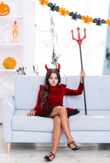 Ragazza graziosa che tiene il tridente di halloween