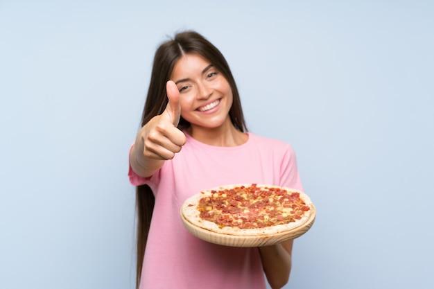 Ragazza graziosa che tiene una pizza sopra la parete blu isolata con i pollici su perché è successo qualcosa di buono