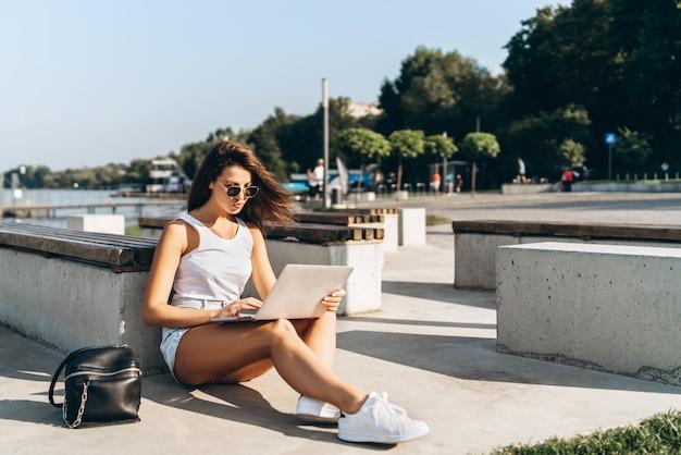 Ragazza graziosa che utilizza computer portatile all'aperto nel parco della città.