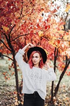 Ragazza graziosa con capelli rossi e cappello che camminano nel parco, tempo di autunno.