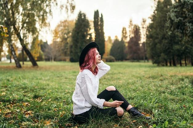 Ragazza graziosa con capelli rossi e cappello che si rilassano nel parco, tempo di autunno.