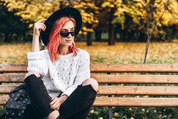 Ragazza graziosa con capelli rossi e cappello che si rilassano sul banco nel parco, tempo di autunno.