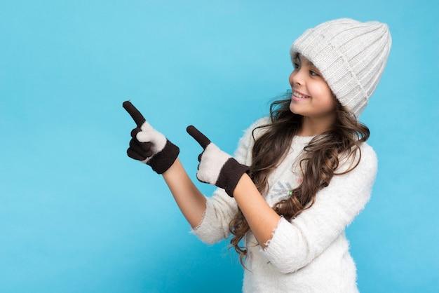 Ragazza graziosa con i guanti che mostrano a destra
