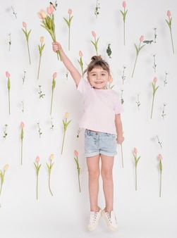 Ragazza graziosa con la foto a figura intera dei tulipani