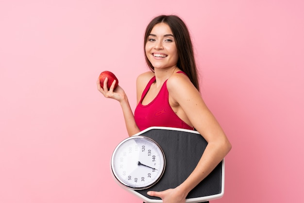 Ragazza graziosa con la pesa sopra la parete rosa isolata con la pesa e con una mela
