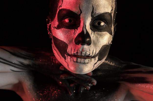 Ragazza graziosa con la pittura di corpo di scheletro di trucco