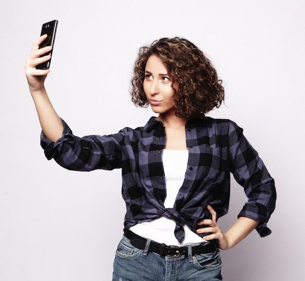 Ragazza graziosa dei pantaloni a vita bassa che prende selfie.