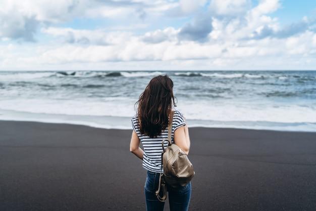 Ragazza graziosa del brunette che cammina sulla spiaggia di sabbia nera.