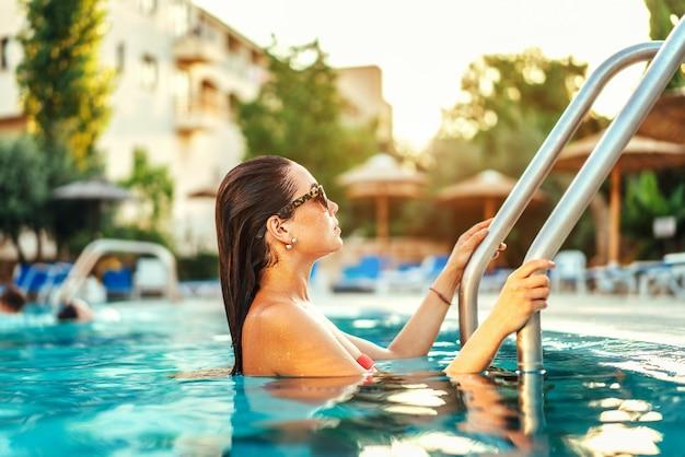 Ragazza graziosa del brunette che si distende alla piscina