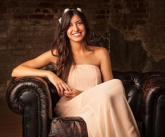 Ragazza graziosa del brunette che si siede sul sofà di cuoio con la priorità bassa del muro di mattoni