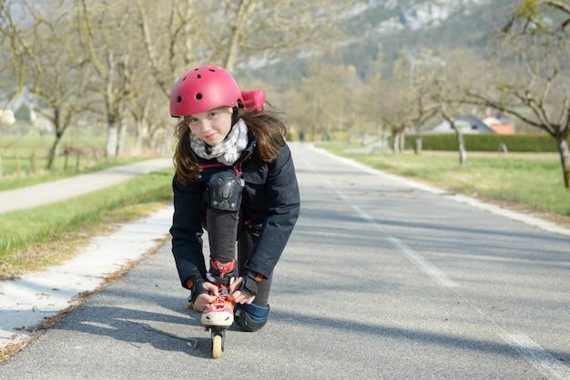 Ragazza graziosa del preteen sui pattini di rullo in casco ad una pista