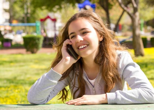 Ragazza graziosa dell'adolescente con lo smartphone mobile del cellpfone al parco di estate