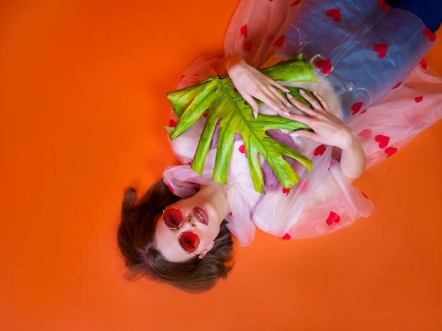 Ragazza graziosa dell'adolescente in un impermeabile con i cuori e gli occhiali da sole rossi che tengono una foglia esotica che si trova su una terra arancio. concetto di moda