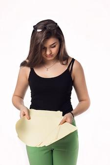 Ragazza graziosa dell'allievo del brunette in pantaloni verdi con i documenti