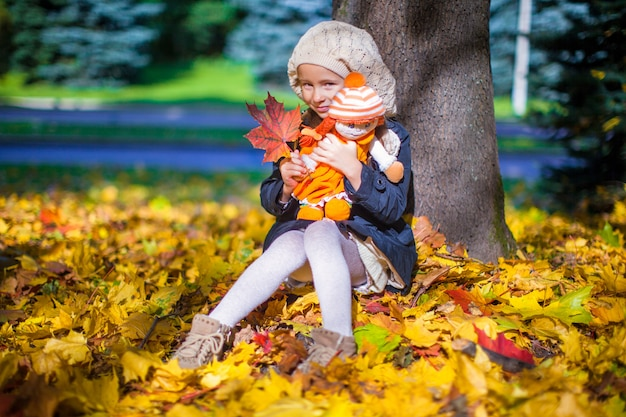 Ragazza graziosa di modo che si siede sotto un albero di acero con la bambola e la foglia rossa il giorno soleggiato di autunno