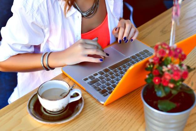 Ragazza graziosa hipster che lavora al suo laptop al caffè della città, luogo di coworking, giovane freelance tocca il taccuino, atmosfera estiva.