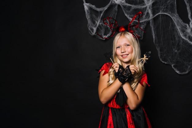 Ragazza graziosa in attrezzatura di halloween con i giocattoli