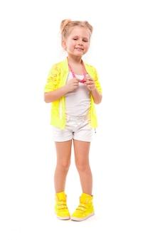 Ragazza graziosa in camicia gialla, pantaloncini bianchi e stivali gialli