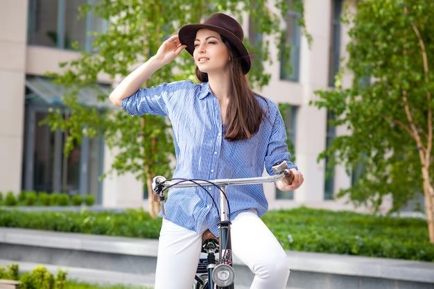 Ragazza graziosa in cappello che guida una bicicletta alla via