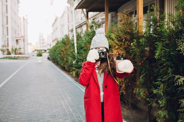 Ragazza graziosa in cappotto rosso e cappello lavorato a maglia che cammina sulla strada. fa foto del caffè in mano.