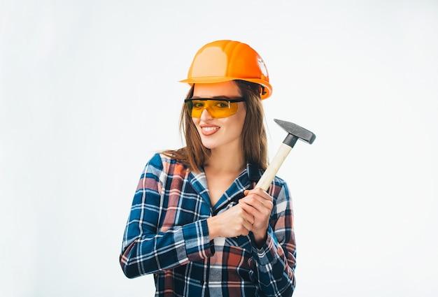 Ragazza graziosa in casco e occhiali di protezione arancio con il martello che sta e che esamina macchina fotografica su bianco