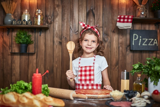 Ragazza graziosa in grembiule a quadretti che cucina pizza