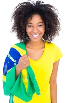 Ragazza graziosa in maglietta gialla che tiene bandiera brasiliana che sorride alla macchina fotografica