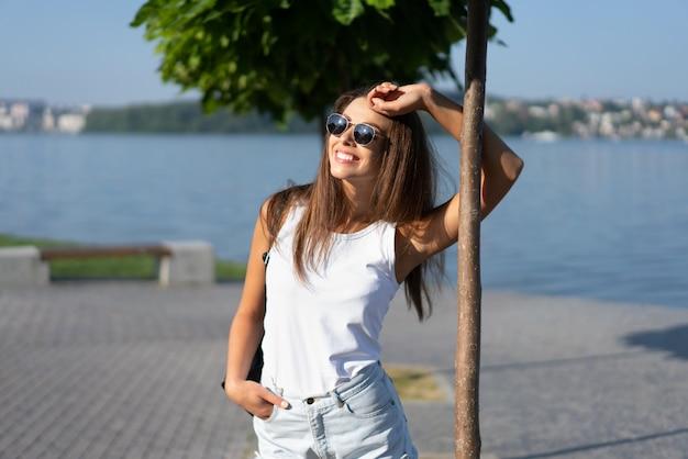 Ragazza graziosa in occhiali da sole rilassante sotto l'albero nel parco.