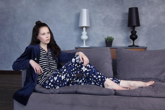 Ragazza graziosa in pigiami blu che posano su uno strato grigio a casa