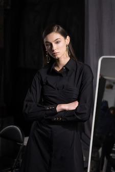 Ragazza graziosa in vestito nero nello spogliatoio vicino allo specchio