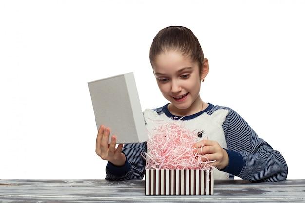 Ragazza graziosa sorpresa che apre il contenitore di regalo