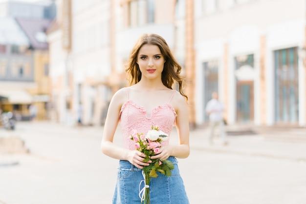 Ragazza graziosa sveglia con trucco professionale in una cima rosa in una città di estate che tiene un mazzo delle rose bianche e rosa
