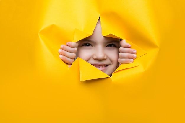 Ragazza guardando attraverso un buco in carta colorata