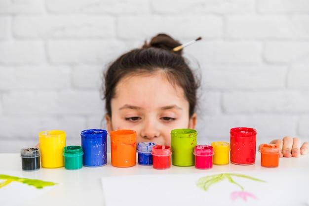 Ragazza guardando le bottiglie di vernice colorata ai margini del tavolo bianco