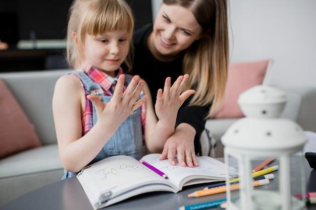 Ragazza guardando le mani mentre si fa i compiti con la mamma