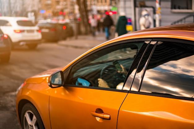 Ragazza guida auto arancione con smart phone in mano. strada cittadina