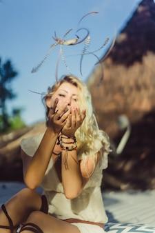Ragazza hippie con lunghi capelli biondi in un abito sul tetto.