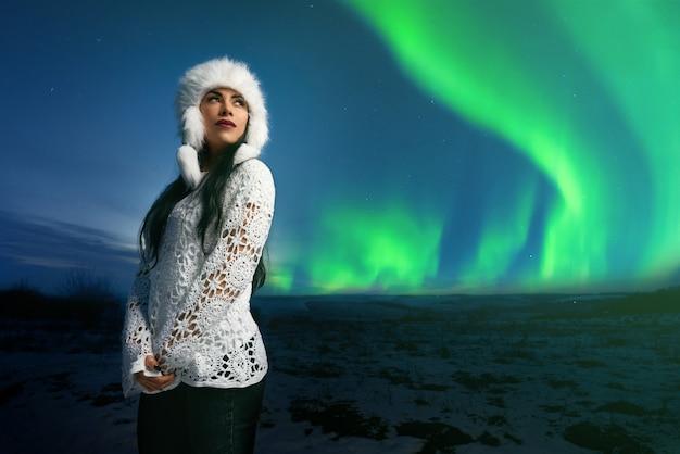 Ragazza in abbigliamento moderno su sfondo di aurora boreale.
