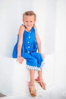 Ragazza in abiti blu divertirsi all'aperto per le strade di mykonos
