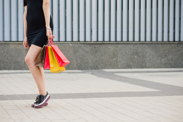 Ragazza in abiti neri in piedi borse di partecipazione