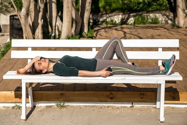 Ragazza in abiti sportivi che si siede sulla panchina e ascolta musica, fitness, motivazione sportiva, sport, fitness