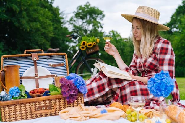Ragazza in abito a scacchi rosso e cappello seduto sul libro di lettura coperta da picnic in maglia bianca e bere vino. picnic estivo in giornata di sole con pane, frutta, bouquet di fiori di ortensia. messa a fuoco selettiva